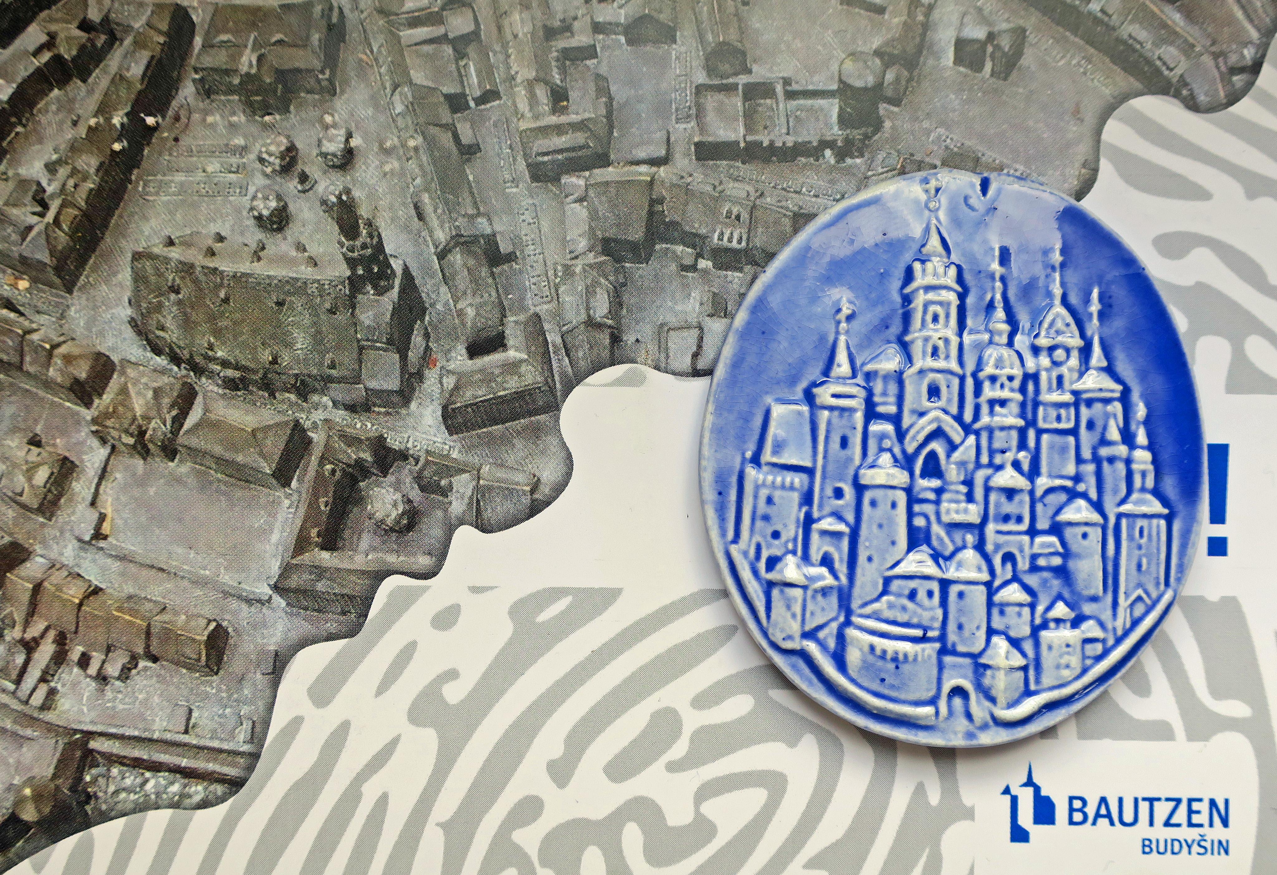 Einladungskarte zur Einweihung des Tastmodells und die blaue Keramikgedenkmünze.