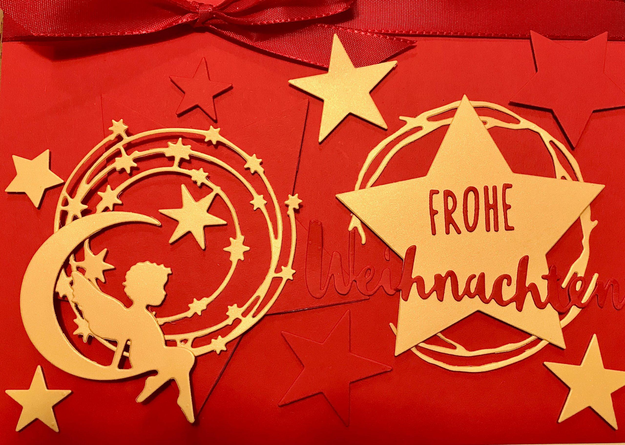 """Weihnachtskarte aus rotem und goldenem Fotokarton. Es gibt einen großen roten Stern, welcher auf der linken Seite der Karte ist. Auf diesem Stern ist ein goldener Sterneschweif im Kreis mit kleinen und großen Sternen. Davor sitzt ein goldener Engel auf der unteren goldenen Mondsichel. Rechts auf der Karte ist ein goldener Weidenkranz. Darüber befindet sich ein großer goldener Stern. Dieser trägt in roter Farbe den Schriftzug """"Frohe Weihnachten"""". Rings herum sind goldene und rote Sterne aufgeklebt. Am oberen Rand der Karte befindet sich eine rote Schleife."""